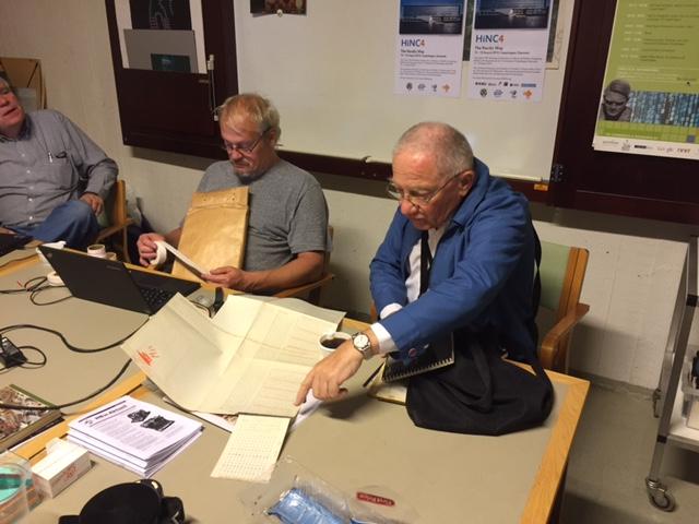 ??? fortæller om hans arbejde, mens Mogens Kjær foretager optisk analyse af en af Sørens hulstrimler. Yderst til venstre sidder Finn Verner Nielsen og lytter med.